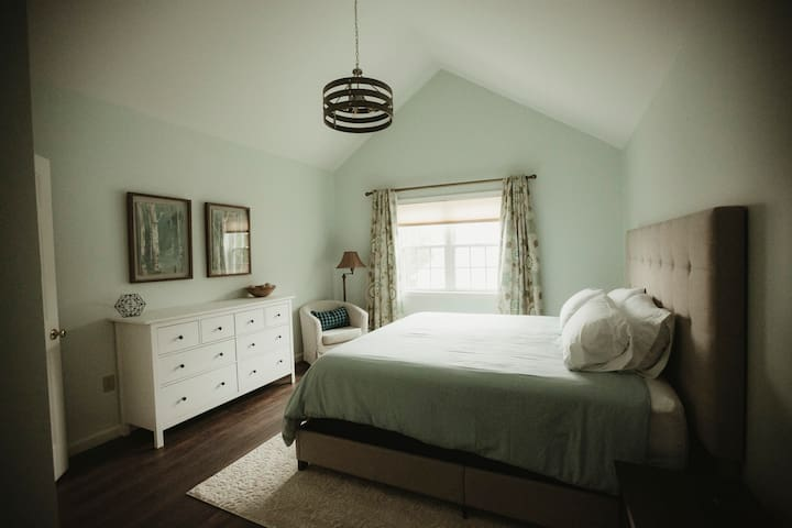 The master bedroom has an en suite bath and an upholstered king bed
