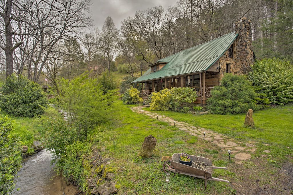 The home's 2-acre property features lush greenery, a trout stream, and Koi pond.