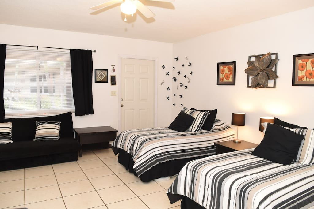 """Sleeping and sitting area with view of patio, shown with beds in """"Twin"""" configuration."""