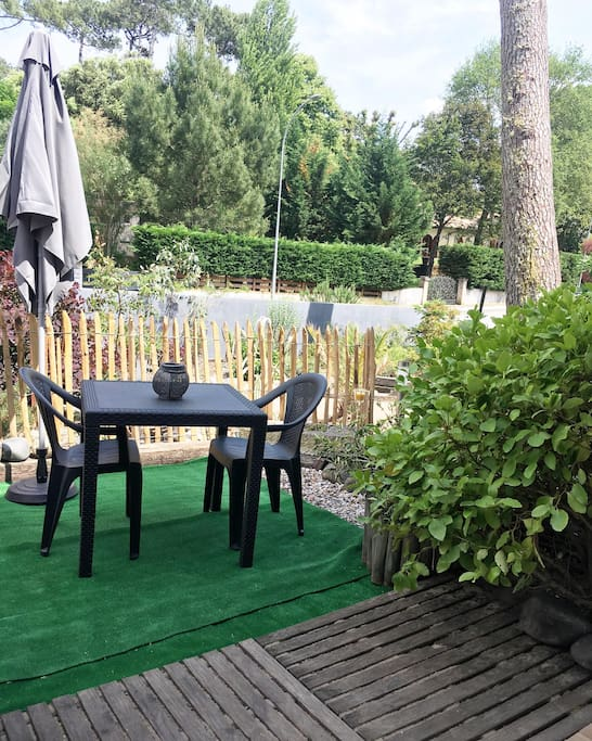 Terrasse privative du studio comprenant table chaises, parasol, étendoir à linge