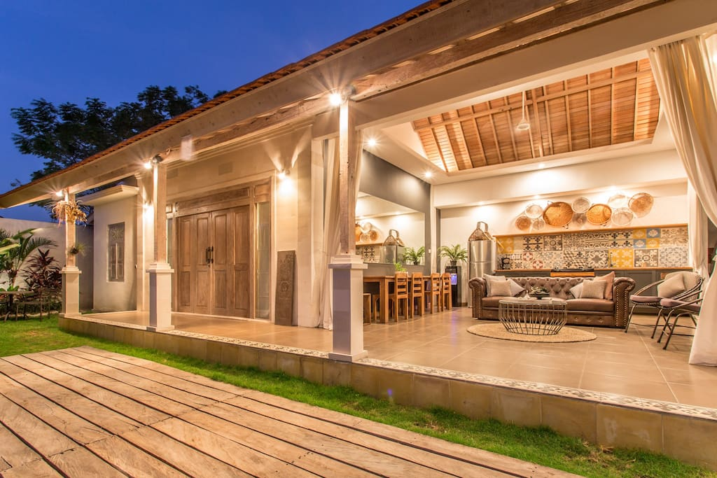 Open style lounge, kitchen, and dining room overlooking the lush tropical gardens and shimmering swimming pool.