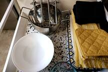 In  bottom kitchen cabinet between refrigerator and stove. We supply serving bowls, strainer, liquid measuring cup, trivets, drying mat, dish towels. dish cloths and pot holders.
