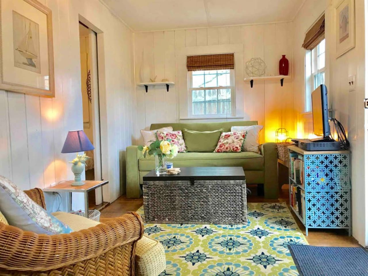 Colorful & charming Tiny House living room. Smart TV, DVD player & a small library. Didn't finish the book? Take it with you!