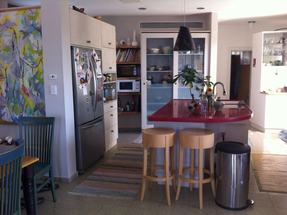 Kitchen with a walk around island and 2 glass doors to balcony