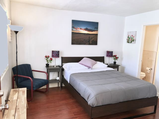 """Bedroom view. comfy queen size bed with Luxurios 13"""" memory foam mattress and spacious living area. All new inside. High Speed Wifi (100MB), Smart TV, Mini fridge and renovated marble bath."""