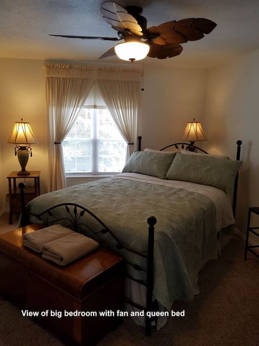 Big bedroom with fan and queen bed