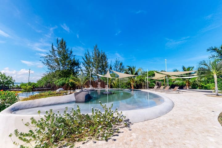 Beachfront retreat with a private hot tub, WiFi, AC, shared pool & lagoon views!