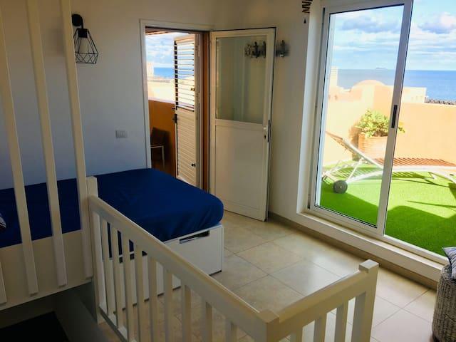 Habitación de la planta alta, abierta a escalera, con cama matrimonio de 1,35x2,00 metros. Y accesos a las dos terrazas de la planta alta.