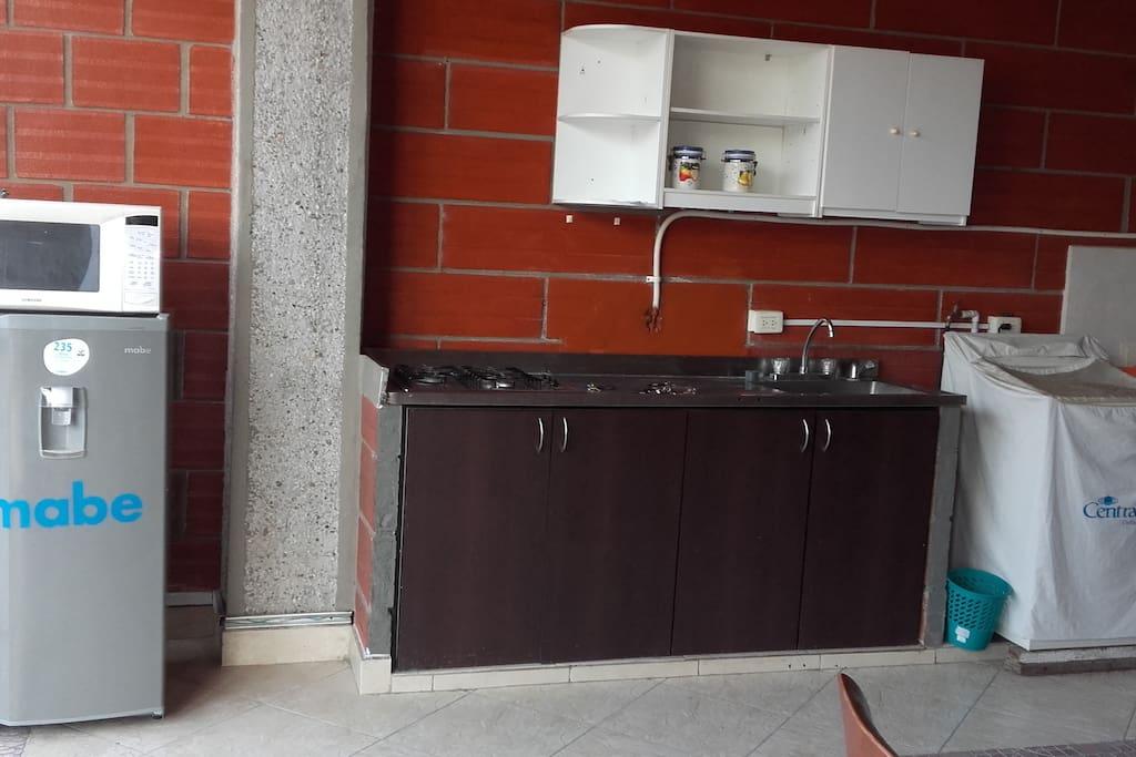 cocina con estufa, nevera y horno microondas