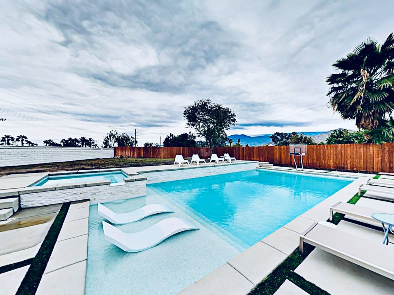 19'x38' size of big private oasis with basketball hoop, tanning deck with in-water chairs/umbrella, and spa surrounded by gorgeous mountain