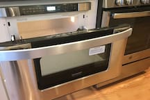 Microwave opens easily like a drawer. there is an oven/stove right next to it.