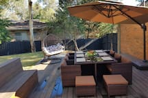Private garden and deck with table, bbq, swinging chair and fire pit
