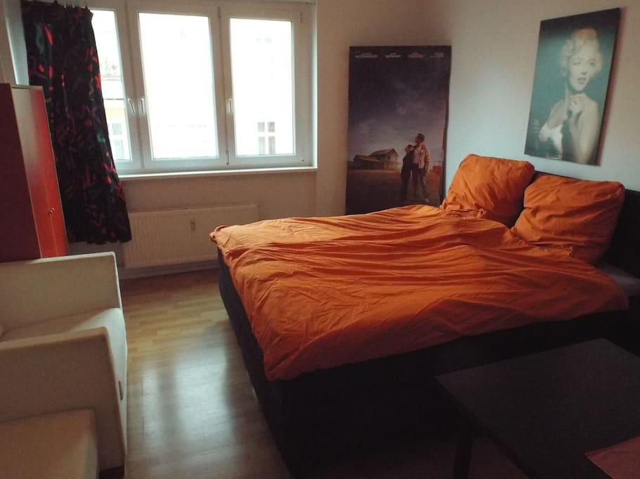 Seitenansicht auf Bett, Sessel und Schrank (rot)