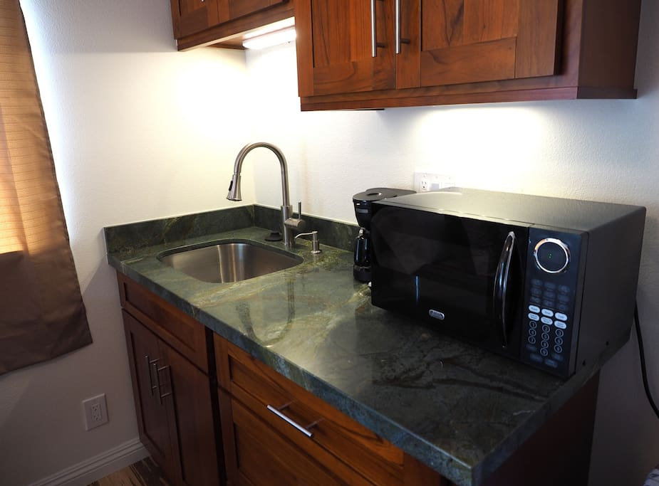 Kitchenette includes coffee maker, microwave, kitchen sink with disposal, compact refrigerator, portable butane gas burner, and utensils, dishes, and pots and pans for cooking,