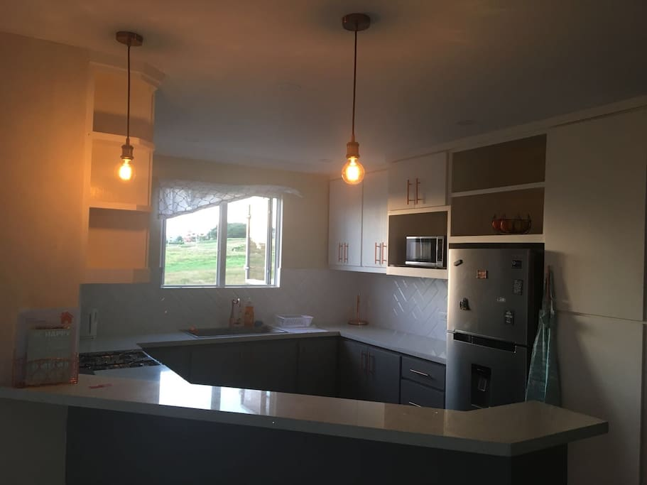 Kitchen with stove, fridge, microwave, kettle, pots and pans, crockery, cutlery and more
