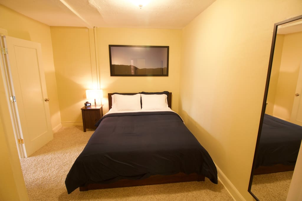 Bedroom features a full size wall mounted mirror, queen bed with luxury linens, closet with hangers and luggage rack, iPhone dock and reading light on a nightstand.