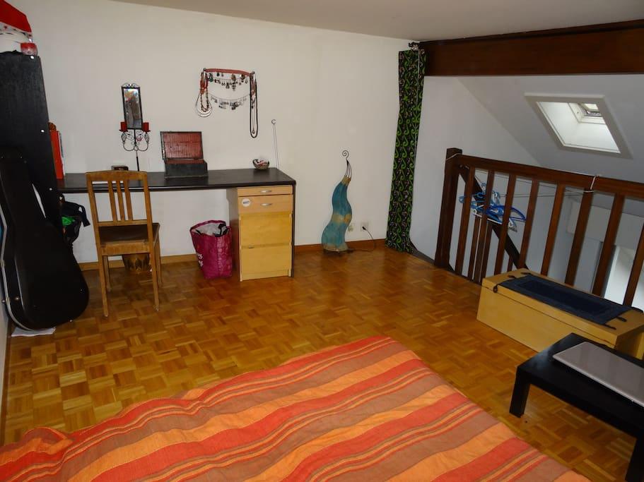 Chambre en mezzanine au dessus du salon, lit double, bureau.  Mezanine bedroom over the living room with a double bed and a desk.