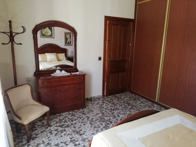 Vista de la habitación de matrimonio desde la cama, donde se puede observar que cuenta con armario empotrado y mueble-coqueta.