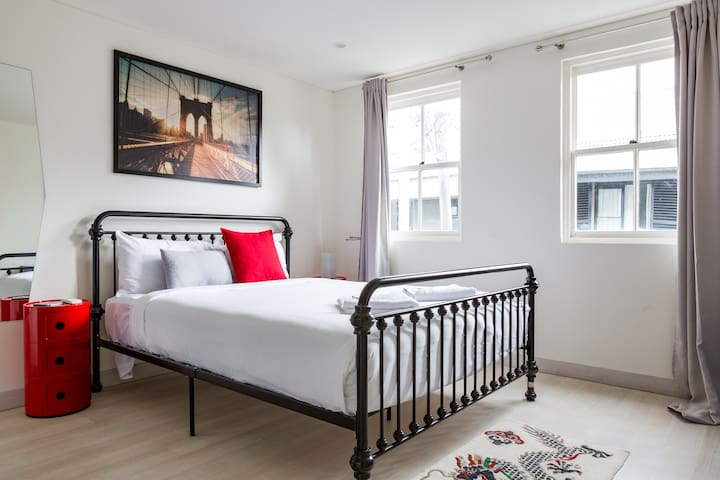 The sunlit second bedroom includes a queen bed topped with luxury linens and ample space for storing your belongings.
