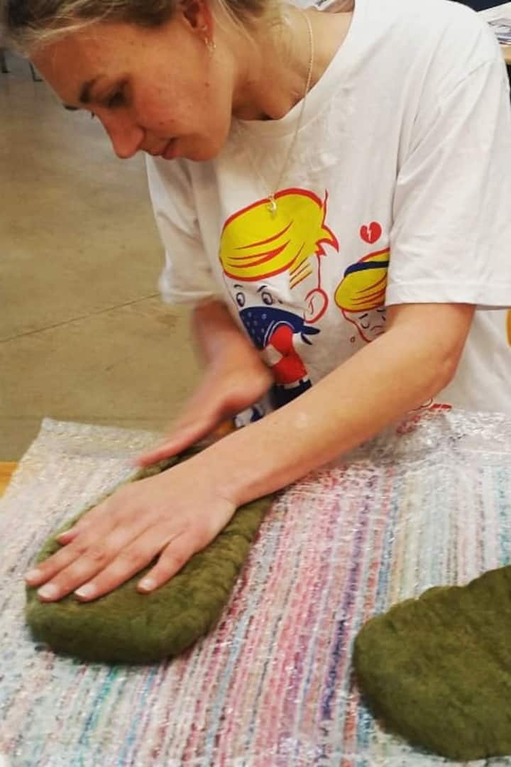 A workshop participant making felt.