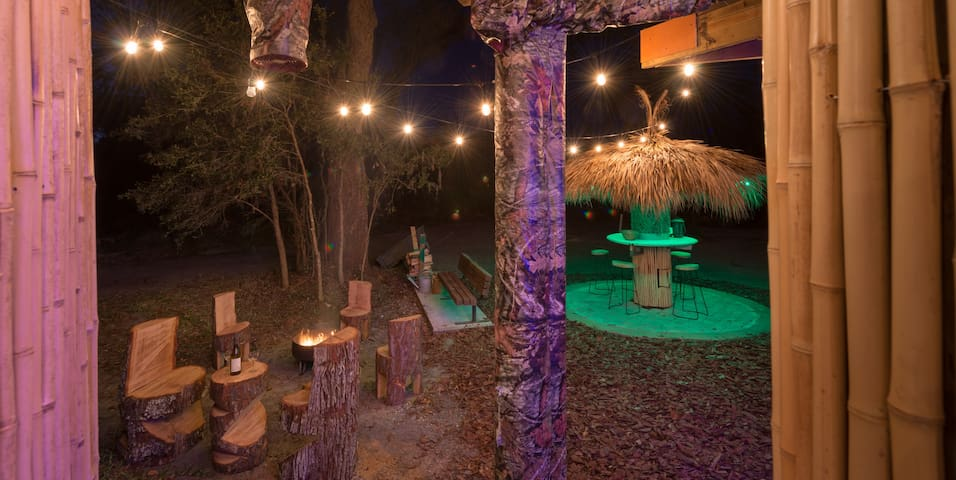 Wood-burning fireplace and tiki hut looking from the hot tub deck
