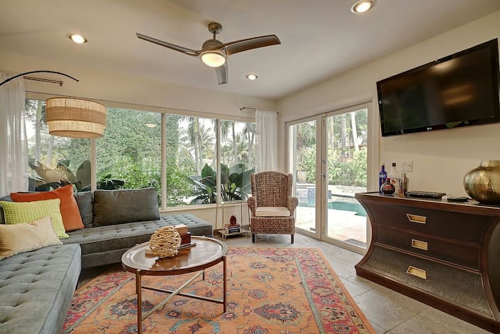 Sun Room is bright and inviting with large flatscreen tv and doors to pool
