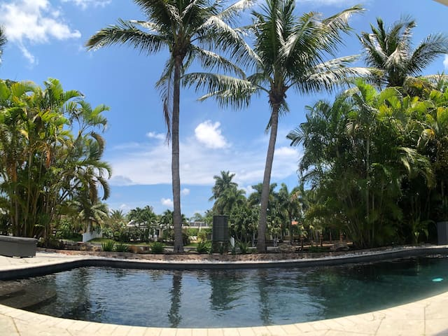 This is your daily view from the wall of glass in the spacious open living room with the waterway just beyond your heated saltwater lagoon style pool