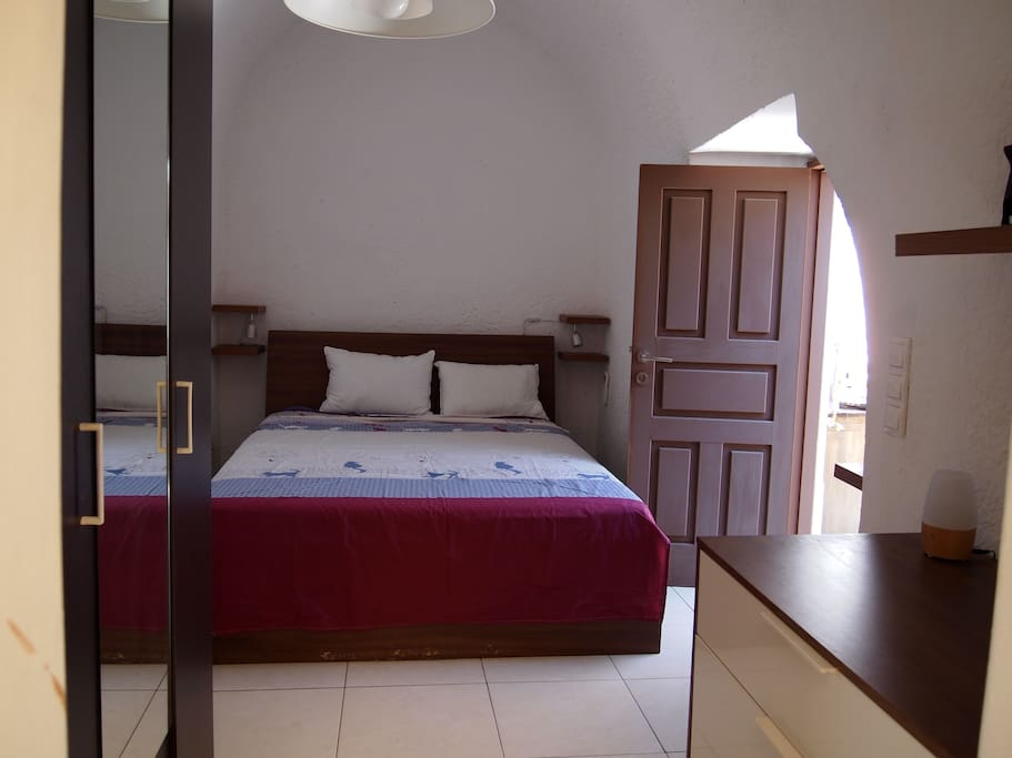 entering the first bedroom,in an arche type room,cool,with a king size bed,a wardrobe and A/C