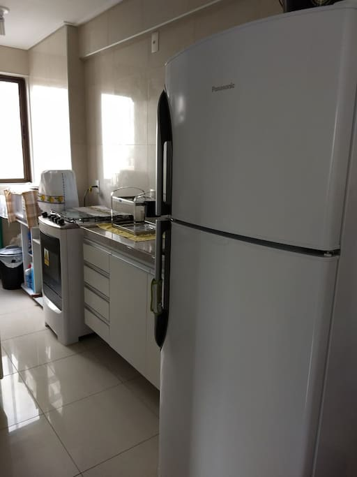 Cozinha + área de serviço com geladeira, fogão, bebedouro natural (água não incluso), microondas, tanque de lavar e varal pequeno.