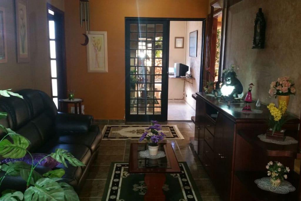Sala de estar e escritório ao fundo.