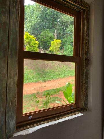 vista do quarto, janela com vidraça e com proteção de tela.