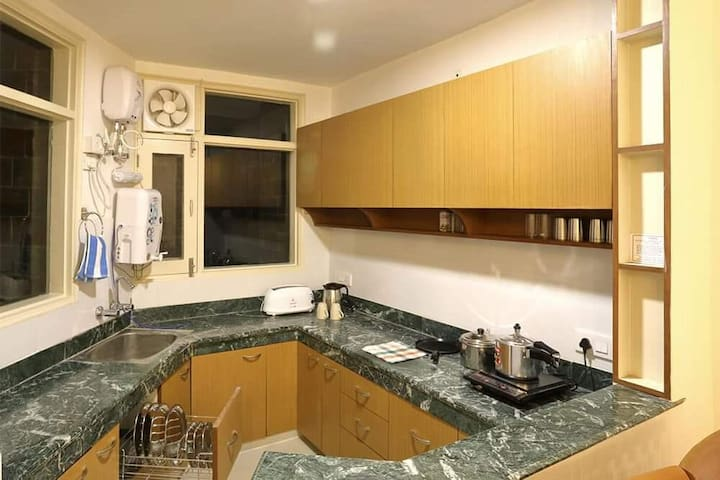 kitchen - it is equipped with an electric kettle, RO system for water, modular kitchen shelves, induction stove, basic utensils for cooking