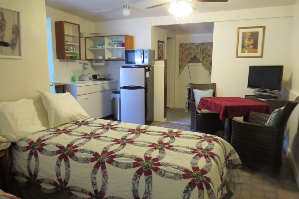 View of twin bed, seating area and kitchenette
