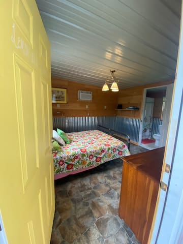 Yellow room on left side of cabin. Queen size bed, in room restroom with rain shower head, air conditioning, and fluffy stack of pillows.