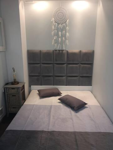 Klimatyczna sypialnia z wygodnym dwuosobowym łóżkiem małżeńskim w szaro-białej kolorystyce i klimatycznym oświetleniem