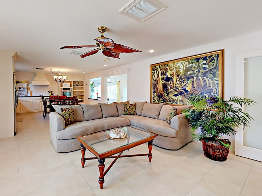 Spacious open-concept living room with plush sectional sleeper sofa and tropical artwork.