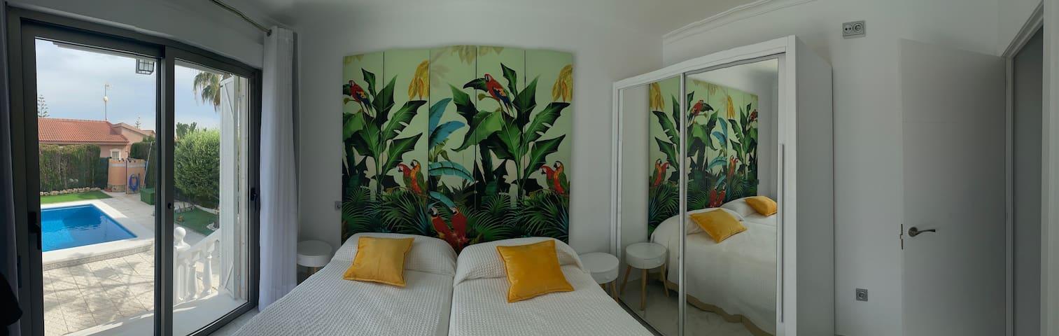 Habitación con cama doble ; armario. Tiene acceso al jardín con piscina.
