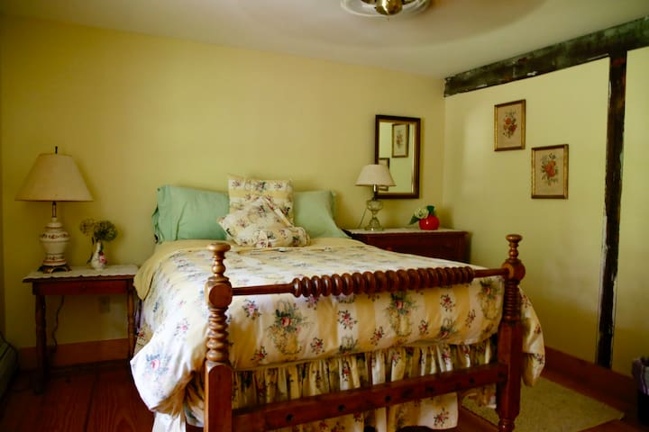 Yellow bedroom. Period oak four poster bed. En-suite bathroom with claw foot tub.