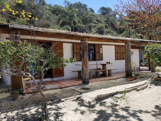 Esta é a varanda, com uma grande mesa para aproveitar as refeições apreciando a vista. No terreno está cheio de pitangueiras com frutas.