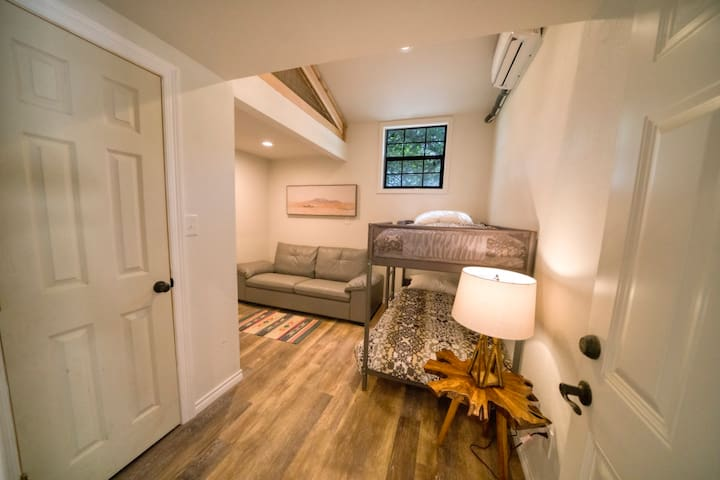 bunk room with two twin bunks and walk-in closet, attached with interior door to corner queen room