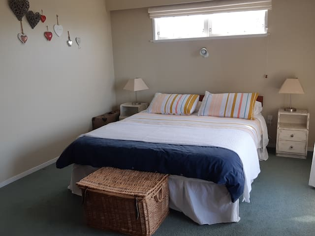 Large main bedroom,  with doors leading out to the front deck. Outdoor furniture and cushions are located in the wardrobe for your use.