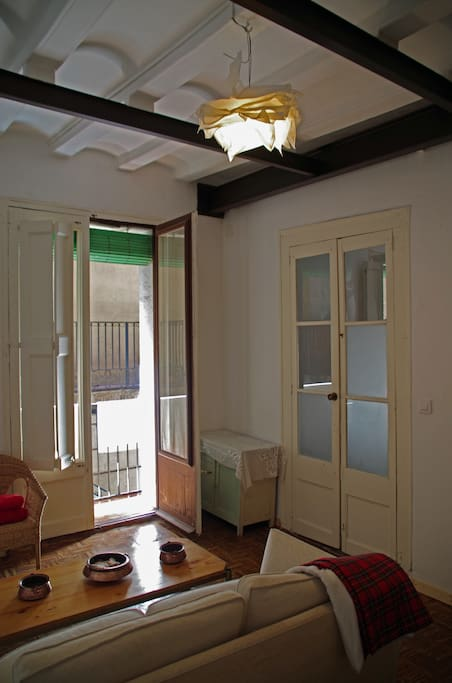 View of door, sofa and french windows from the bed. You can see the high ceilings, wooden beams and reinforced metal beams.