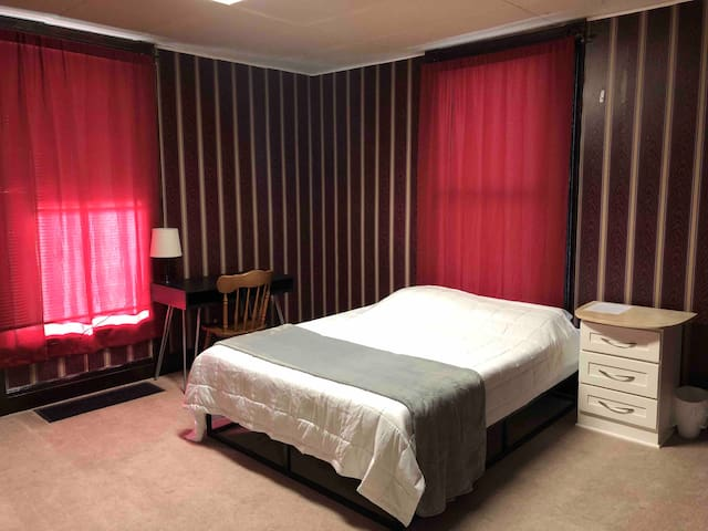 Private bedroom with queen size bed and desk.