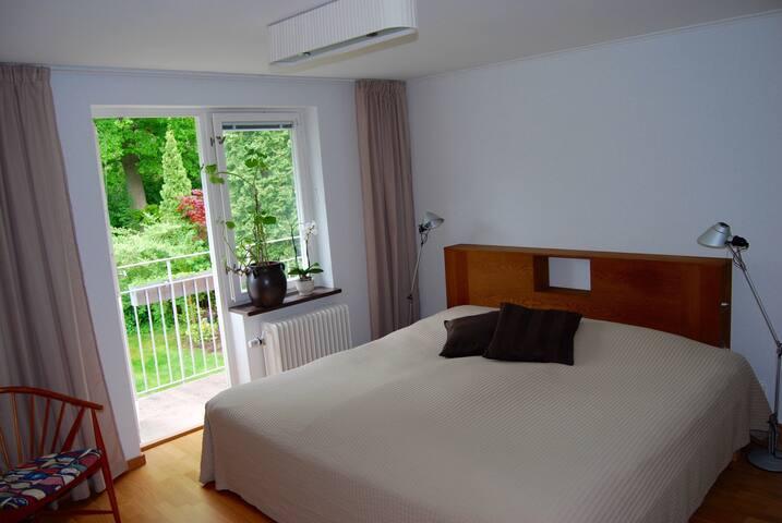 Stort sovrum med 210cm bred säng och utgång till balkong.
