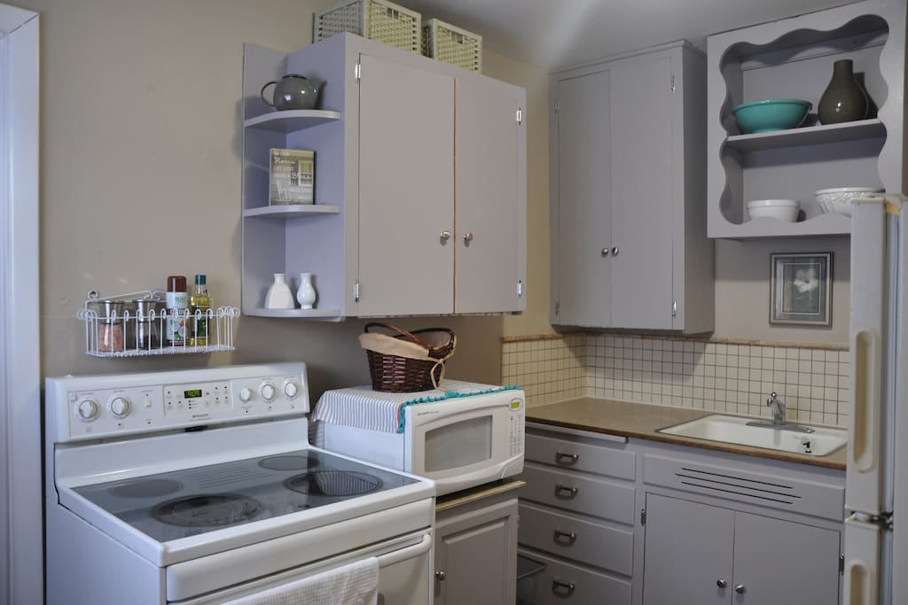 fully stocked small kitchen with range, microwave and full fridge