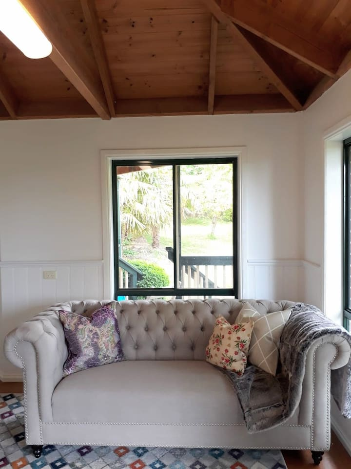 enjoy relaxing on the couch watching a movie or chatting with friends, trees outside all windows
