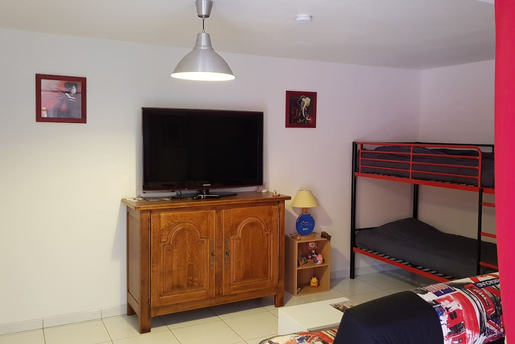 Salon et coin montagne Lits superposés,  clic clac et grande TV à écran plat