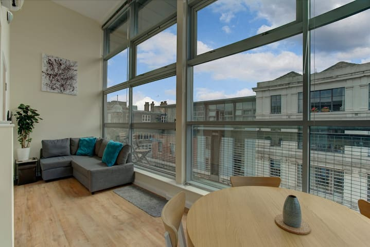 Bright & spacious living area with floor to ceiling windows