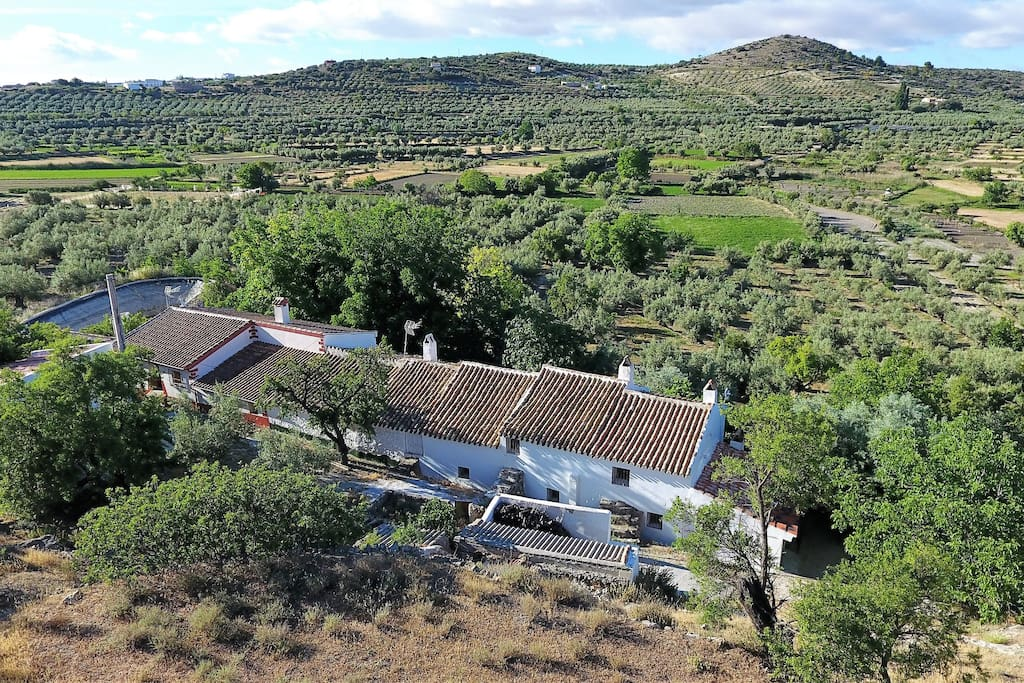 The farmhouse stands at the foot of a rocky hillside, overlooking olive and almond groves.