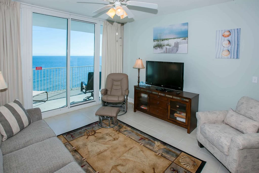 Living room with flat screen TV and private balcony access